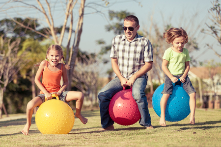 healthy sport: Dad and children playing on the lawn in front of house at the day time Stock Photo