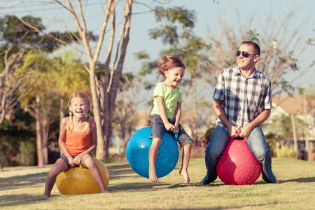 family outside: Dad and children playing on the lawn in front of house at the day time Stock Photo