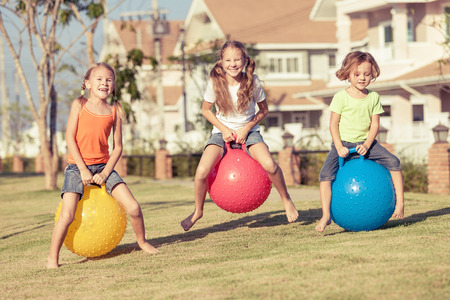 family outside: happy kids playing with inflatable balls on the lawn in front of house at the day time