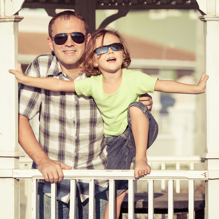 vacation home: Father and son playing near the house at the day time. They sitting in the white gazebo. Concept of friendly family. Stock Photo