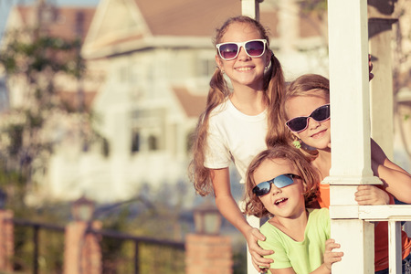 family outside: happy kids playing near the house at the day time. They sit in the white gazebo. Concept of friendly family. Stock Photo