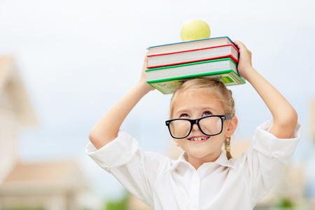 niños en la escuela: Retrato de hermosa niña de la escuela que parece muy feliz al aire libre en el día. Tema de la escuela Concepto.