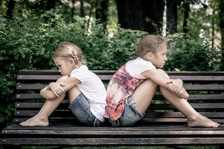 niños tristes: dos triste hermana sentada en el banco en el parque en el día Foto de archivo