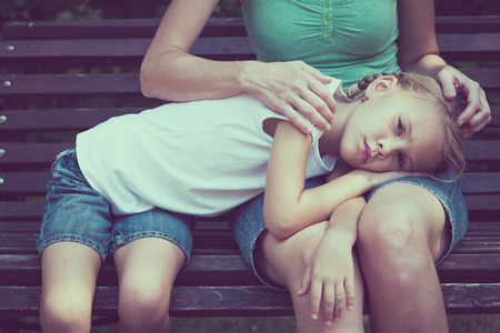 asustadotdo: Madre e hija sentada en el banco en el parque en el día.