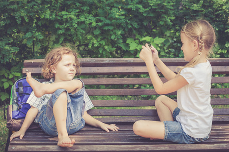 sitting on bench: Two happy children  playing in the park at the day time. Concept Brother And Sister Together Forever
