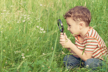 discovery: Happy little boy exploring nature with magnifying glass at the day time Stock Photo