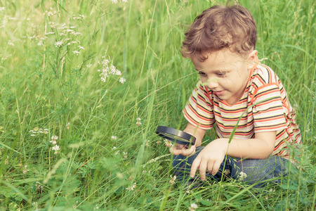children face: Happy little boy exploring nature with magnifying glass at the day time Stock Photo