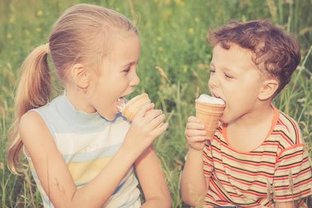 comiendo helado: Dos niños felices jugando en el parque en el tiempo del día. Concepto Hermano y hermana Juntos para siempre Foto de archivo