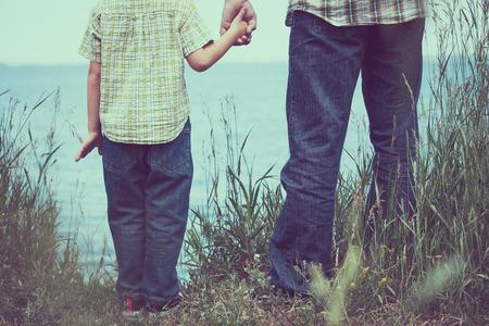 父と息子の一日の時間で湖の近くの公園に立っています。フレンドリーな家族の概念。