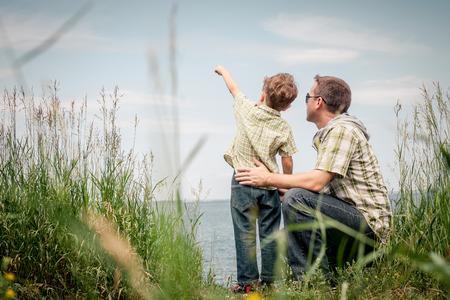 父と息子の一日の時間で湖の近くの公園で遊んで。フレンドリーな家族の概念。