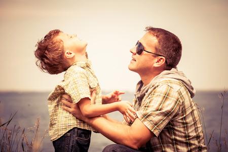 padres: Padre e hijo que juegan en el parque cerca del lago en el tiempo del d�a. Concepto de la familia.