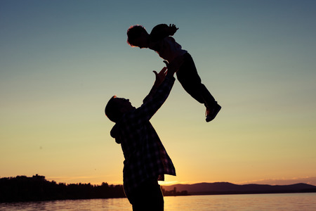 father's: father and son playing on the coast of lake in the mountains of at the sunset time Stock Photo