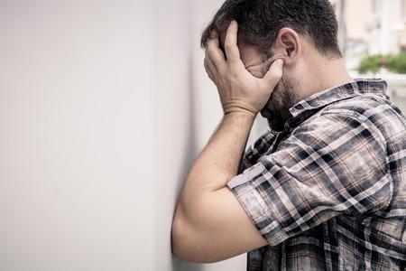 ansiedad: retrato de un hombre triste que se coloca cerca de una pared y cubre su rostro en el día