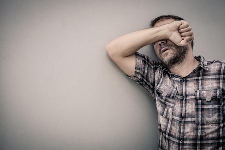 homme triste: portrait d'un homme triste debout près d'un mur et couvre son visage au jour Banque d'images