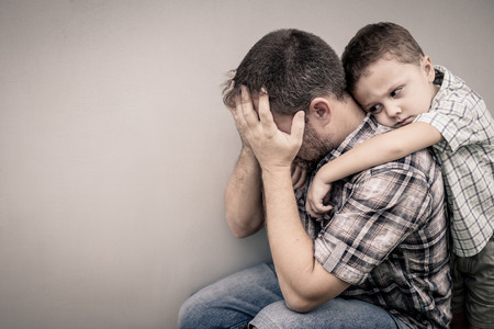 unhappy people: sad son hugging his dad near wall at the day time Stock Photo