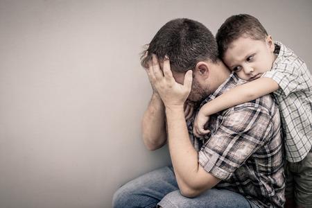 traurigen Sohn umarmt seinen Vater in der Nähe von Wand an der Tageszeit Lizenzfreie Bilder