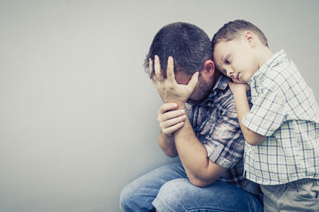 sad son hugging his dad near wall at the day time Standard-Bild