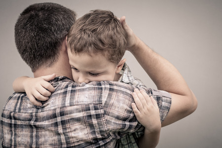 upset: sad son hugging his dad near wall at the day time Stock Photo