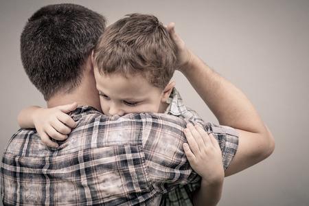 crying boy: triste hijo abrazando a su padre cerca de la pared en el momento día