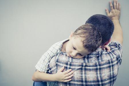 grief: sad son hugging his dad near wall at the day time Stock Photo