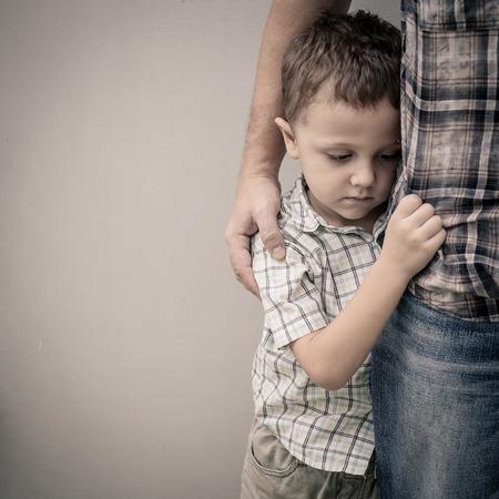maltrato infantil: triste hijo abrazando a su padre cerca de la pared en el momento día