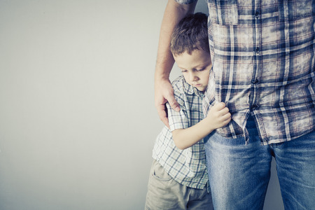 fear: sad son hugging his dad near wall at the day time Stock Photo