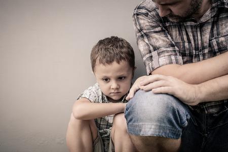 traurigen Sohn umarmt seinen Vater in der Nähe von Wand an der Tageszeit Standard-Bild