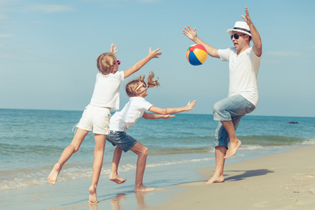 family vacation: Father and daughters playing on the beach at the sunset time. Concept of friendly family. Stock Photo
