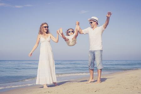 Gelukkig gezin wandelen op het strand van de dag de tijd. Concept van de vriendelijke familie.