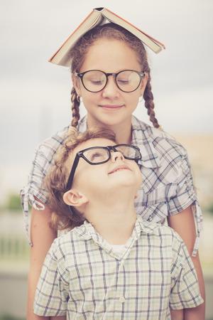 niño y niña: Retrato de hermoso niño de la escuela y una niña mirando muy feliz al aire libre en el día. Tema de la escuela Concepto.