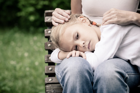 grief: Sad mother and daughter sitting on bench in the park at the day time.