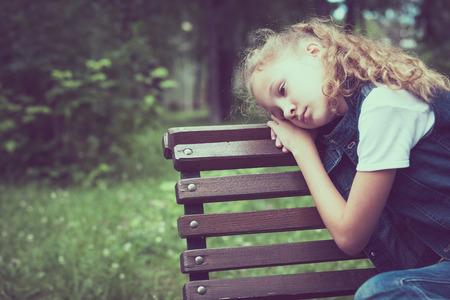 Portret van triest blond meisje, zittend op een bankje op het moment van de dag.