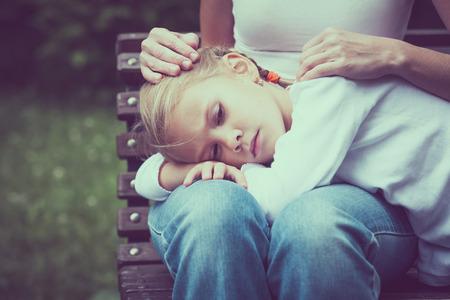 madre: Madre e hija sentada en el banco en el parque en el día.