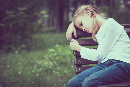 Portrait of sad blond little girl sitting on bench at the day time.