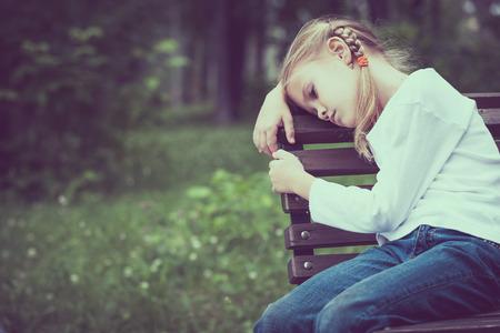 mujeres y niños: Retrato de triste niña rubia sentada en el banco en el momento en día.
