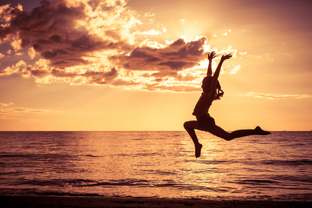 kids having fun: Happy girl jumping on the beach at the sunset time Stock Photo