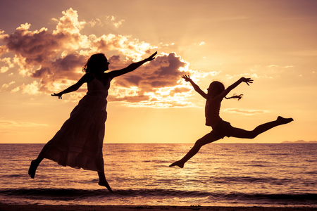 mother and  daughter playing on the beach at the sunset time Stock Photo