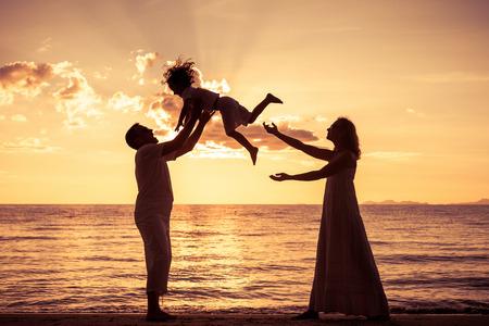 Silueta de la familia feliz que juega en la playa en la puesta del sol. Concepto de la familia.