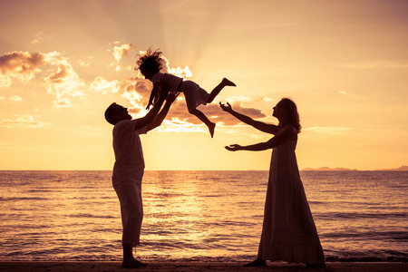 happy family: Silhouette of happy family who playing on the beach at the sunset time. Concept of friendly family. Stock Photo