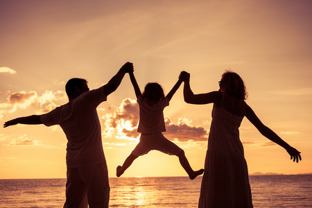 family: Silhueta da família feliz que joga na praia no momento do por do sol. Conceito de família amigável.
