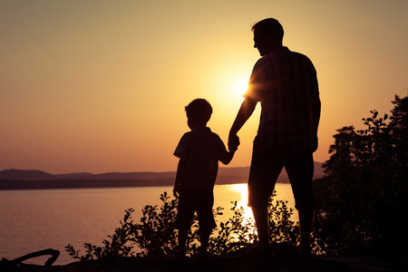 father and son playing on the coast of lake in the mountains of at the sunset time Stock Photo