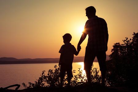 gente feliz: padre e hijo jugando en la costa del lago en las montañas de la puesta del sol en el momento