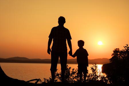 아버지와 아들은 일몰 시간에 산에 호수의 해안에서 재생