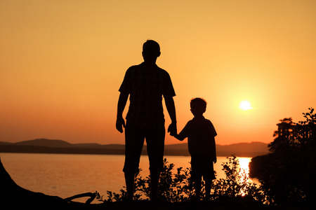 father and son playing on the coast of lake in the mountains of at the sunset time Foto de archivo