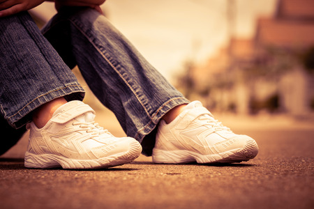 youth: White youth sneakers on girl legs on road during sunny  summer day. Stock Photo