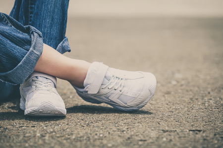 youth sneakers on girl legs on road during sunny  summer day. Stock Photo