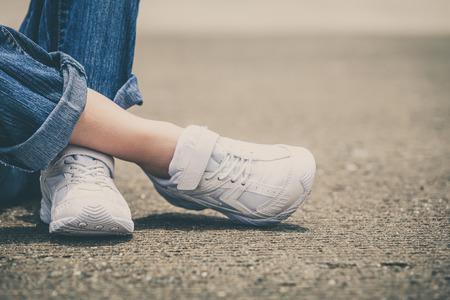 juventud: zapatillas de deporte de la juventud en las piernas de niña en la carretera durante el día soleado de verano.