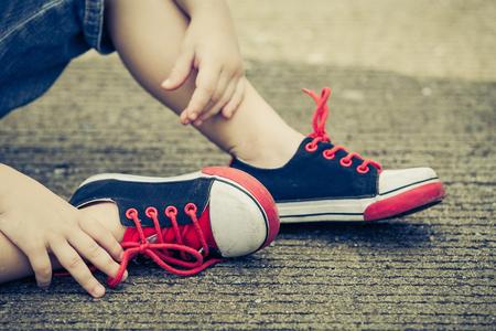 pie bebe: zapatillas de deporte de la juventud en las piernas del muchacho en la carretera durante el día soleado de verano.