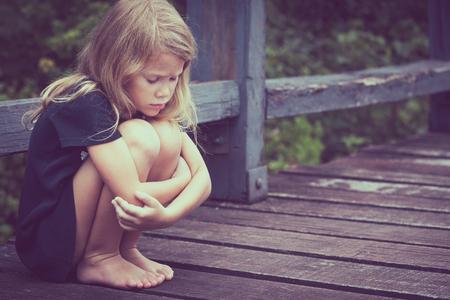 pequeño: Retrato de niña triste rubia sentada en el puente en el tiempo del día