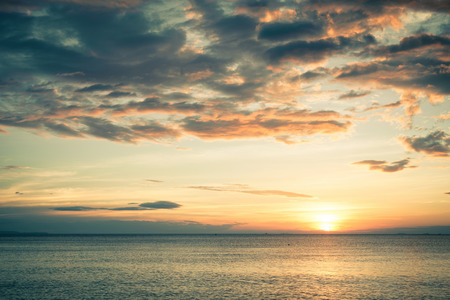 cloudy: Sunset on the beach with cloudyl sky Stock Photo